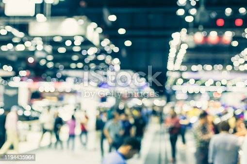 Blur event hall in large exhibition center with people walking background people