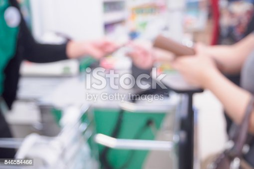 istock Blur female customer hand giving credit card to cashier at supermarket checkout defocused background 846584466