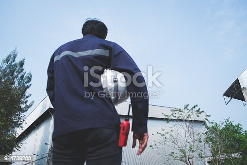 istock Blur foreground image of asian engineer in safety uniform holding white security helmet and walkie-talkie against industry plant and blue sky background for industrial concept 914739288