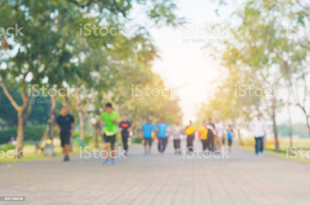 blur group of people exercise with running or jogging on the morning with sun light in the park for healthy. stock photo