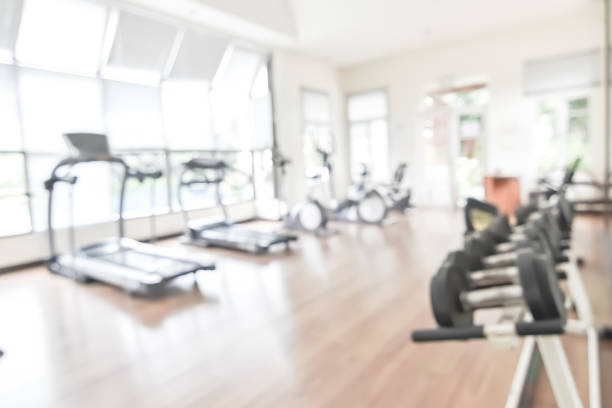 Blur gym background fitness center or health club with blurry sports exercise equipment for aerobic workout and bodybuilding Blur gym background fitness center or health club with blurry sports exercise equipment for aerobic workout and bodybuilding health club stock pictures, royalty-free photos & images