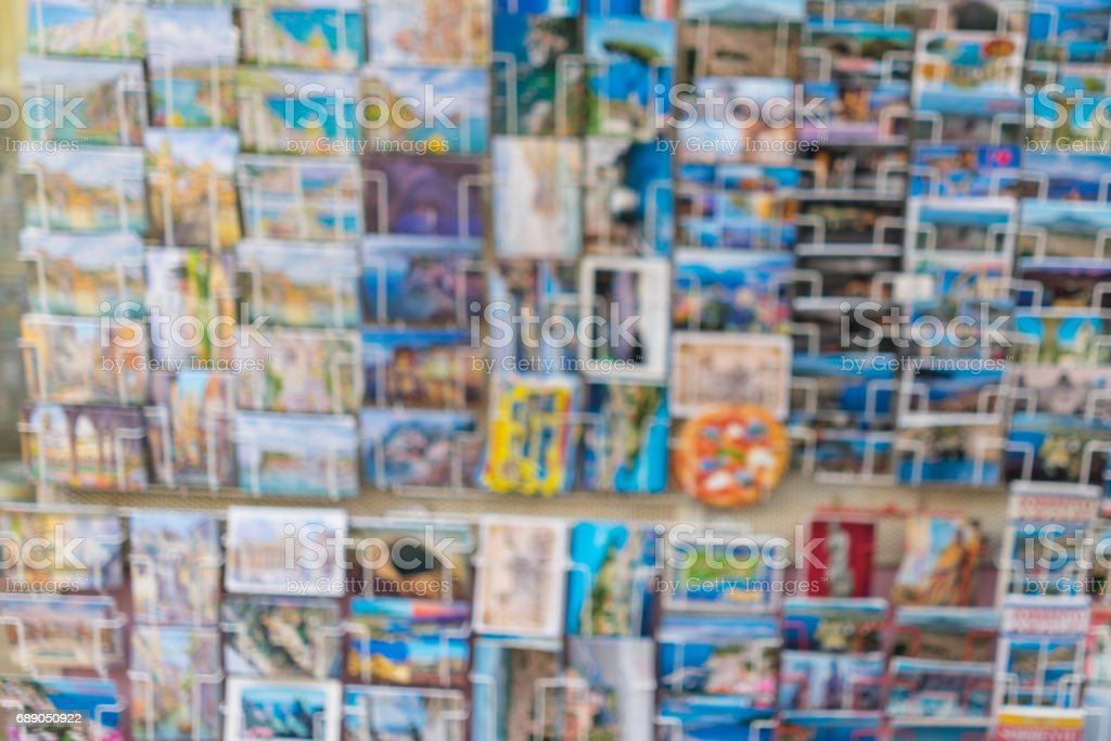 blur image of greeting travel colourful postcards on display in a store shelf as background stock photo