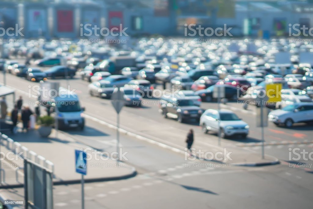 Blur image of parking next to modern shopping mall at peak hour , public transport stop. For background abstract stock photo