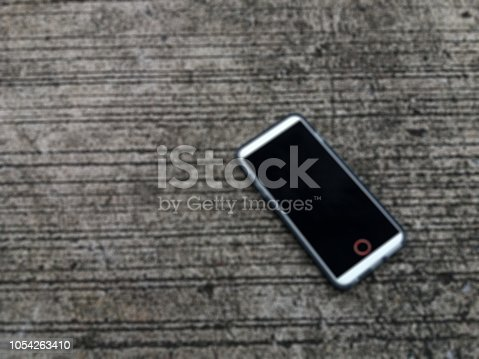 istock Blur mobile phone on cement floor. 1054263410