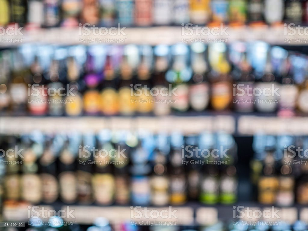 Blur of bottles of beer  on Shelf in Supermarket stock photo