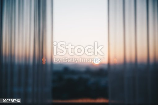 Blur of open curtain at the window of room. View of mountain and morning sunlight.