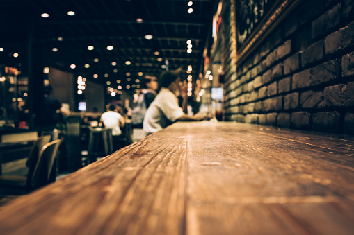 Blur of wood bar table in night cafe /selective focus