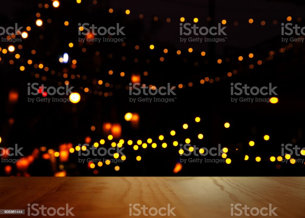 blur orange yellow party light in the dark night bar with top of wood table background stock photo