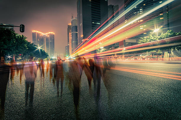 blur people and traffic on a street at night blur people and traffic on a street at night, long exposure. long exposure stock pictures, royalty-free photos & images