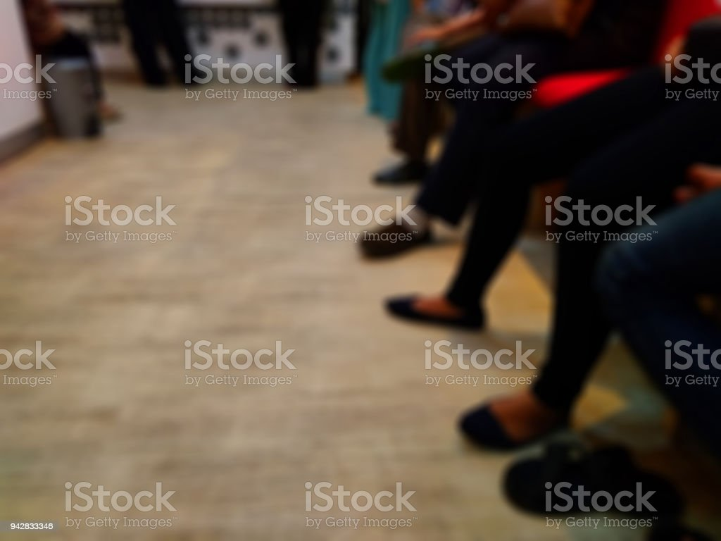 Blur Photo, queue of feet sitting people at indoor customer service stock photo