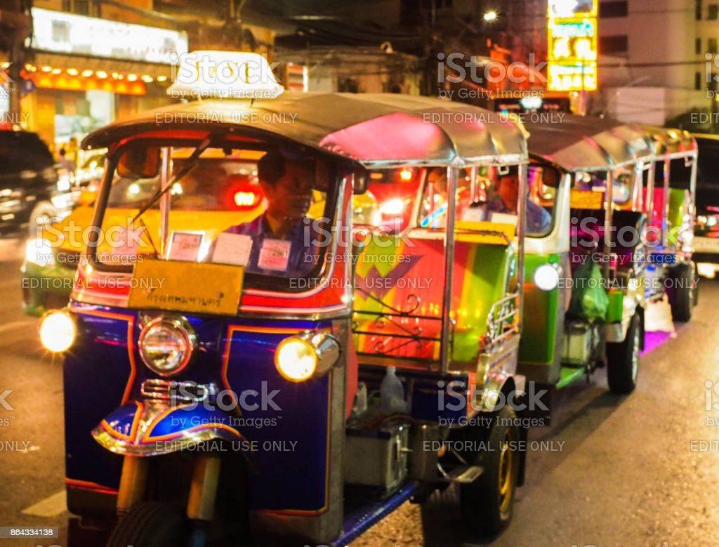 Blur photo.Tuk tuk waiting for the queue for get the customer, tuk tuk is taxi in Thailand. stock photo