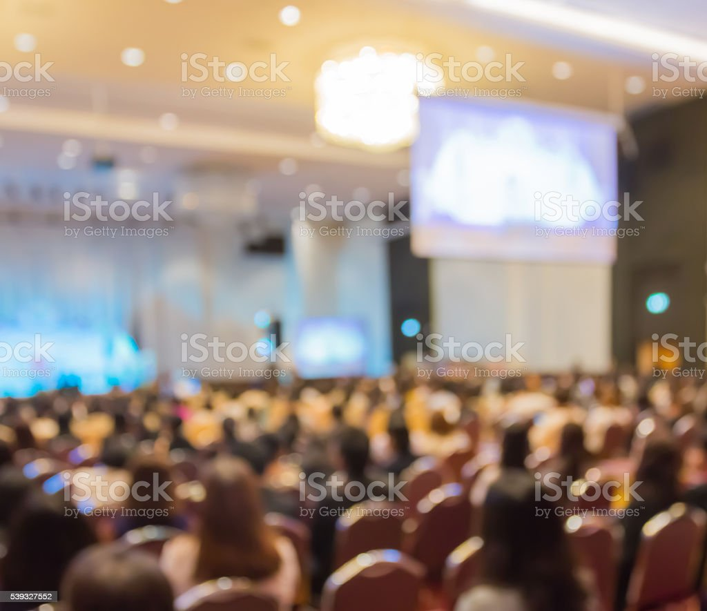 Blur row  of  audience  sitting  in auditorium with screen stock photo
