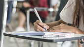 istock Blur school background university students writing answer doing exam in classroom 1011590346