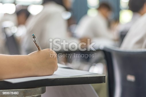 963192098 istock photo Blur school background university students writing answer doing exam in classroom 989978460