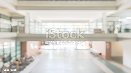 istock Blur school or educational office building interior background in empty hallway indoor area with corridor, glass wall blurry view toward exterior light bokeh 1052673368
