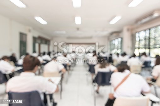 istock Blur school student exam background  in university class with blurry view from back of the classroom of young people having stress doing examination admission test in classroom for education 1127432589