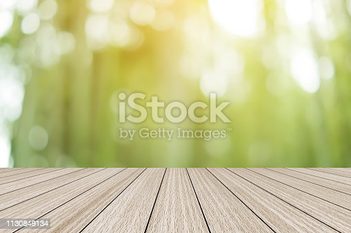 istock blur soft green color organic nature background with glow sunny light and aged plain wood table top perspective view for promote product concept. 1130849134
