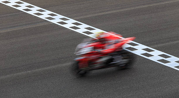blur superbike crossing checkered finish line - motorbike racing stock photos and pictures