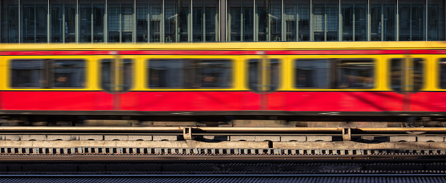 Blur yellow red train in motion, office building background