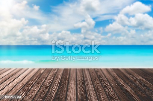Blur tropical beach with bokeh sun light wave on empty old nature wood table abstract background. Product presentation in nature. Vintage tone filter color style.