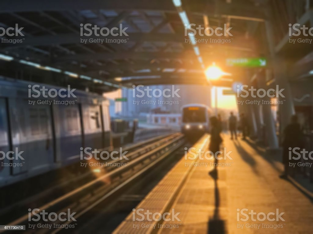 Blur Unidentified people waiting sky train in the morning with flare stock photo