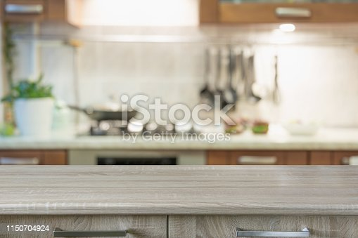 istock Blurred abstract background. Modern kitchen with tabletop and space for display your products. 1150704924