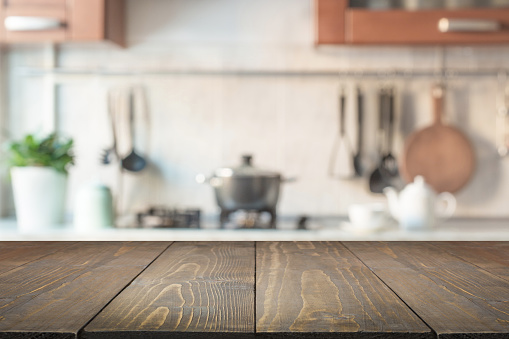 Blurred abstract background. Modern kitchen with wooden tabletop and space for display or montage your products.