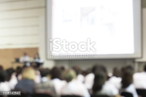 istock Blurred abstract background of business or educational conference seminar in auditorium hall 1128142542