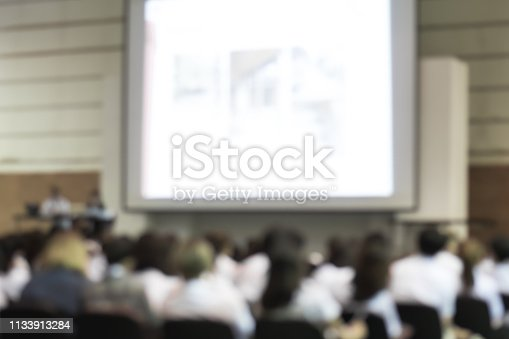 istock Blurred abstract background of business or educational conference seminar in auditorium hall 1133913284