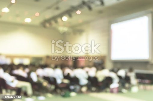 istock Blurred abstract background of educational conference in auditorium hall with students sitting in seat rows and presenters on stage 1130377313