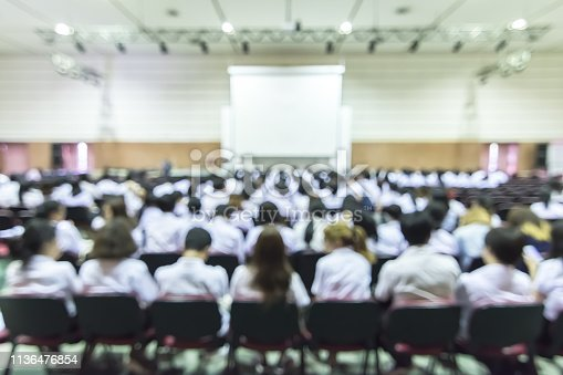 istock Blurred abstract background of educational conference in auditorium hall with students sitting in seat rows and presenters on stage 1136476854