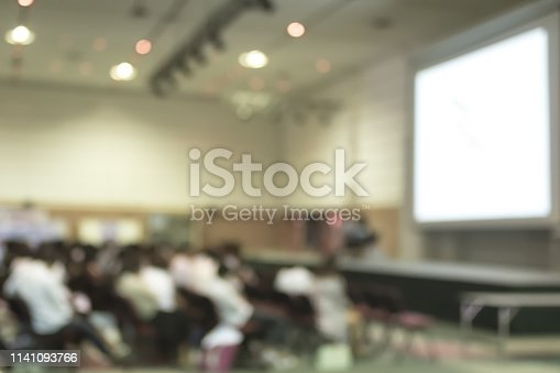 istock Blurred abstract background of educational conference in auditorium hall with students sitting in seat rows and presenters on stage 1141093766