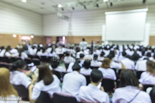 istock Blurred abstract background of educational conference in auditorium hall with students sitting in seat rows and presenters on stage 1155089058