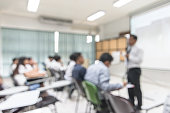istock Blurred abstract background university students sitting in seminar lecture room with teacher in front of class 1066357874