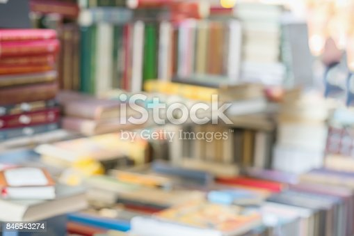 istock Blurred abstract books, textbooks, fiction in rows lying on table, on shelves in library, in modern urban bookshop. Self-study, educational, school, study concept 846543274