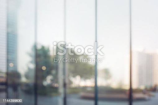 924418868 istock photo Blurred abstract glass wall from building in city town 1144399830