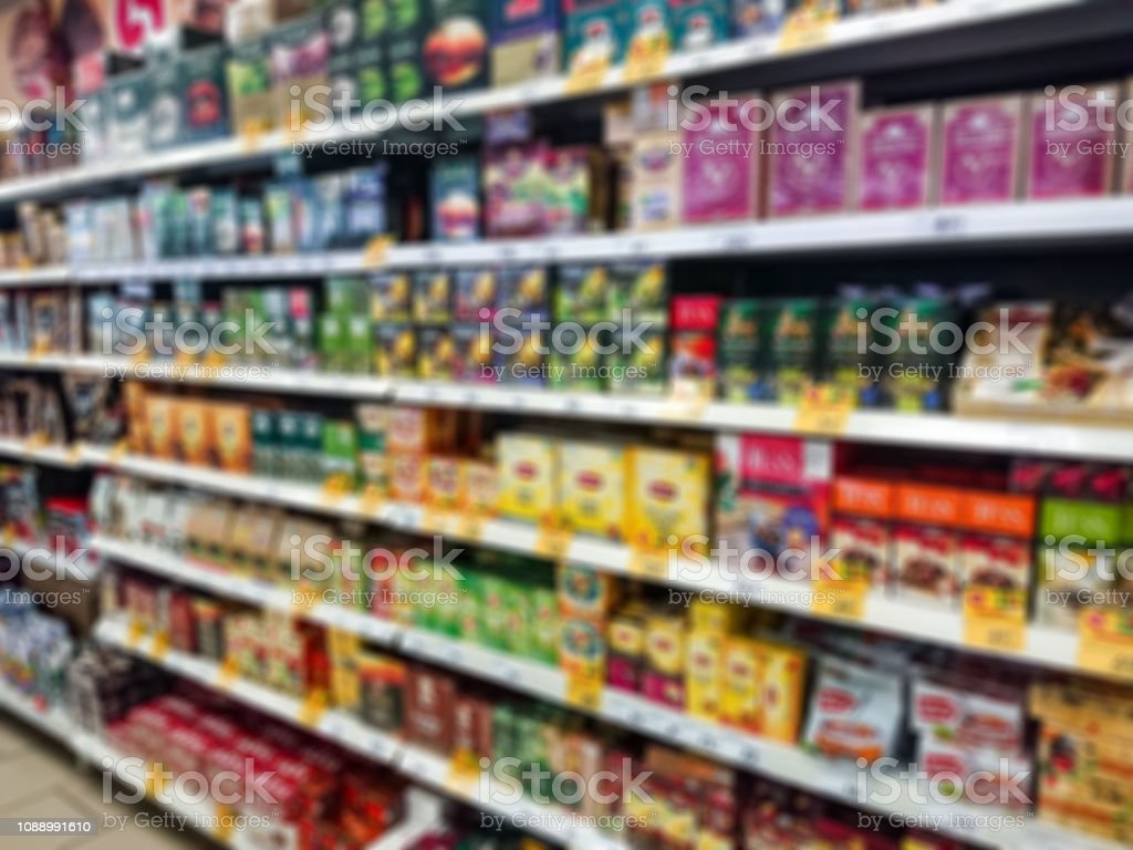 Blurred abstract image. Goods on the shelf of a grocery store. Tea...