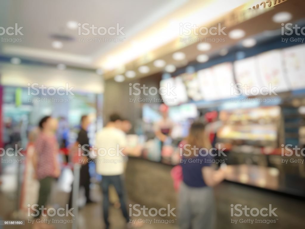 blurred abstract image of people standing for wait to order some food and make payment in fast food restaurant. Use as background image. vintage tone color and light effect. stock photo