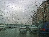 Blurred abstract image of the street, apartment building and cars through a glass with raindrops. City scenes in the Rain. Cityscape through the window. Real life during rainy sad overcast weather.