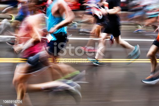 A blurred group of marathon runners running on a city street.