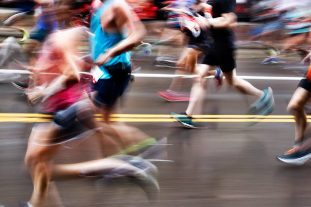 blurred action of marathon runners on city street - marathon stock photos and pictures