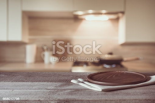 istock Blurred and abstract background. Empty wooden tabletop and defocused modern kitchen background for display or montage your products. Toned image. 668012798