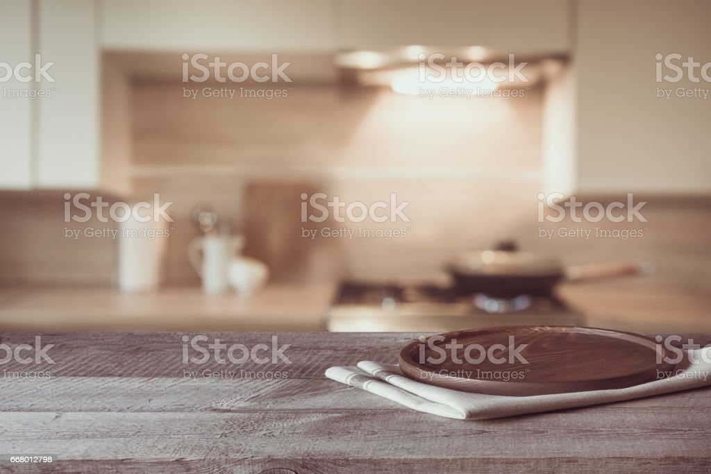 Blurred and abstract background. Empty wooden tabletop and defocused modern kitchen background for display or montage your products. Toned image. stock photo