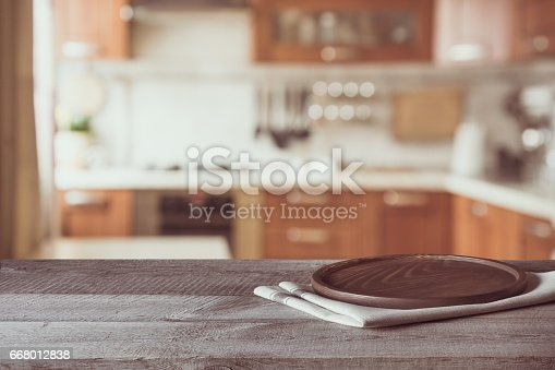 istock Blurred and abstract background. Empty wooden tabletop and defocused modern kitchen background for display or montage your products. Toned image. 668012838
