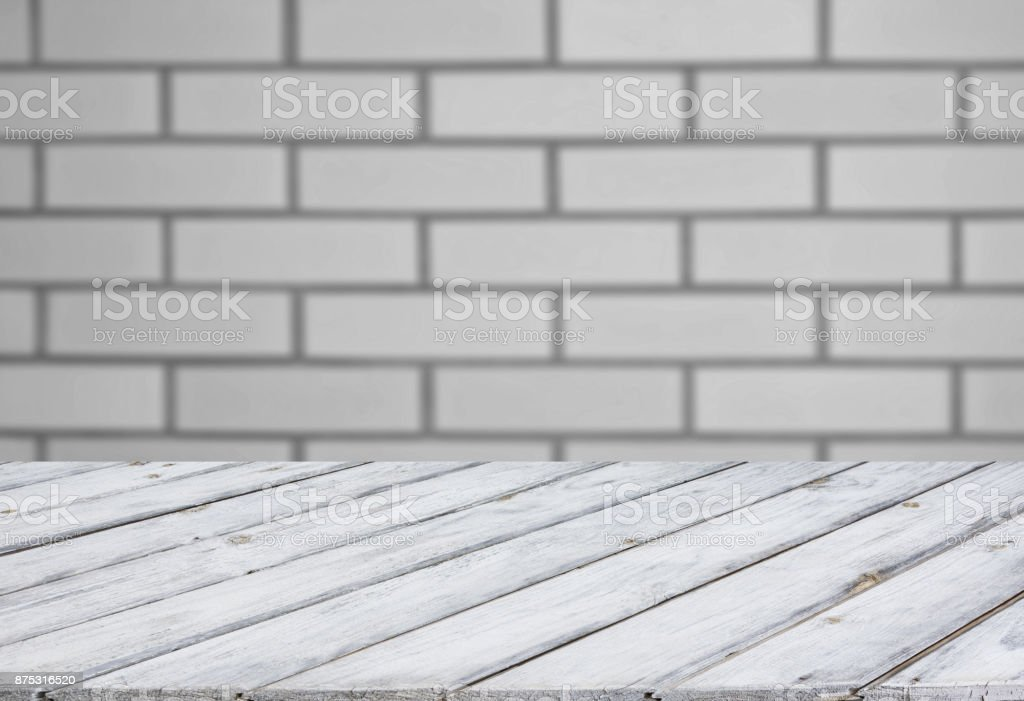 Blurred and abstract background. Empty wooden tabletop and defocused brick wall background for display your products. stock photo