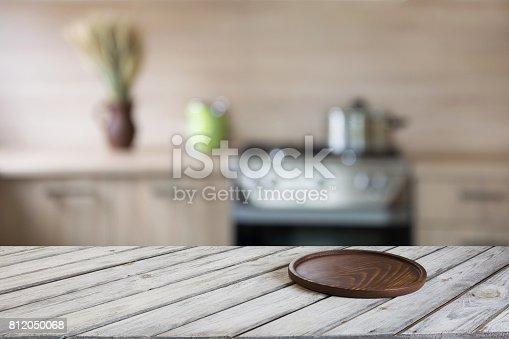 istock Blurred and abstract kitchen background. Empty wooden tabletop with cutting board  and defocused modern kitchen for display or montage your products. 812050068