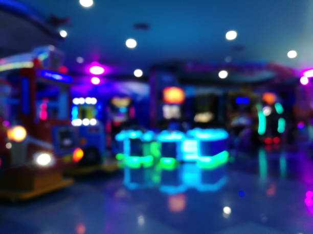 blurred arcade machine game for children game play  in department store. Playground with colorful neon lights and bokeh light. Colorful absract background. stock photo
