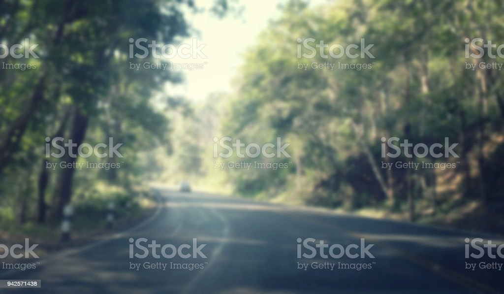 Blurred Asphalt road through the forest, gree natural background stock photo
