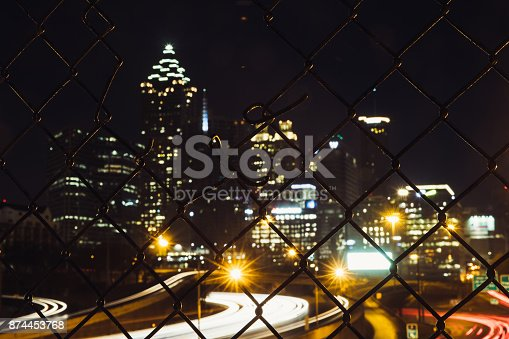 Urban background image of blurred downtown Atlanta through the metal fence with a hole.
