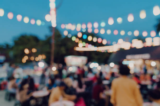 blurred background at night market festival people walking on road. blurred background at night market festival people walking on road. night market stock pictures, royalty-free photos & images